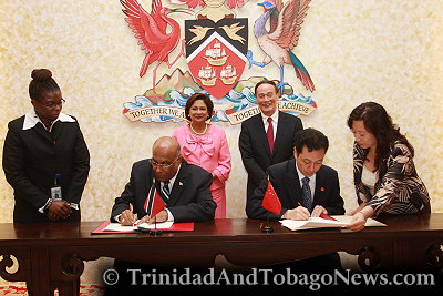 Trinidad and Tobago's Prime Minister Kamla Persad-Bissessar (rear left) and Chinese Vice Premier Wang Qishan (rear right) attend a signing ceremony for an intergovernmental agreement between the two countries at the Diplomatic Centre in St. Ann's Port of Spain, Trinidad and Tobago, on Monday, September 12, 2011.