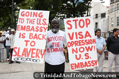 Addil Abdullah held placards protesting U.S. visa policy during the Emancipation Celebrations in Port of Spain