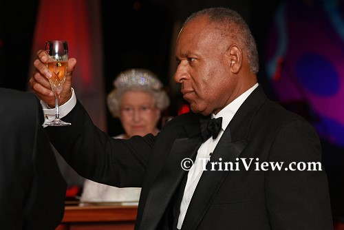 PM Patrick Manning raises his glass (with British Queen in the backdrop) during the State Dinner at President's House for Her Majesty, Queen Elizabeth II